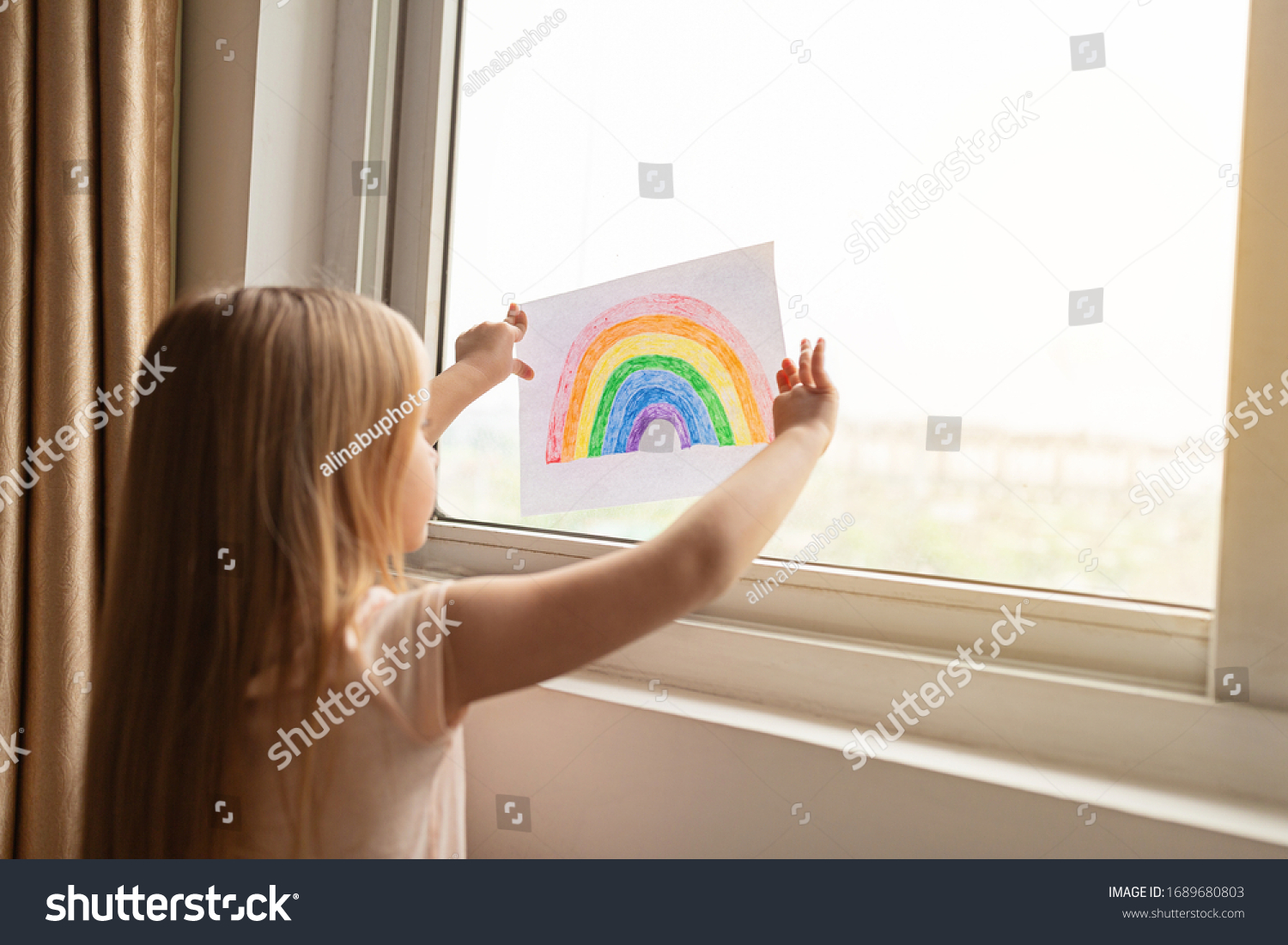 Kid painting rainbow during Covid-19 quarantine at home. Girl near window. Stay at home Social media campaign for coronavirus prevention, let's all be well, hope during coronavirus pandemic concept #1689680803