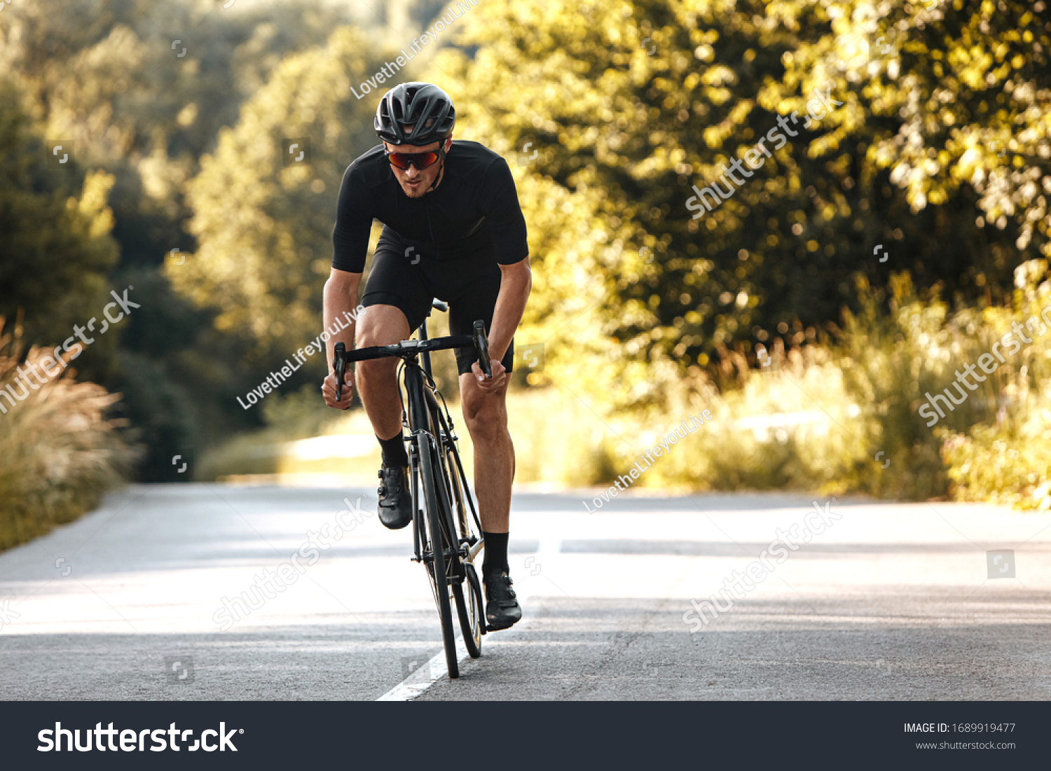 Full length portrait of active man in sport clothing and protective helmet riding bike with blur background of summer nature. Concept of workout and races. #1689919477