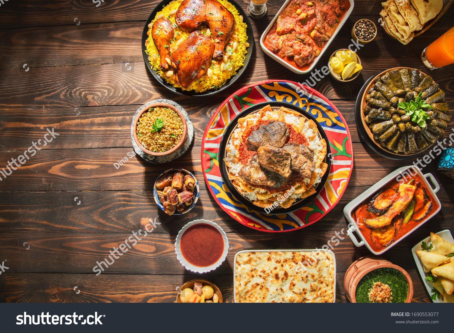 "Arabic Cuisine: Middle Eastern traditional lunch. It;s also Ramadan ""Iftar"" . The Meal eaten by Muslims after sunset during Ramadan. Assorted of Egyptian oriental dishes. Top view with copy space. #1690553077"