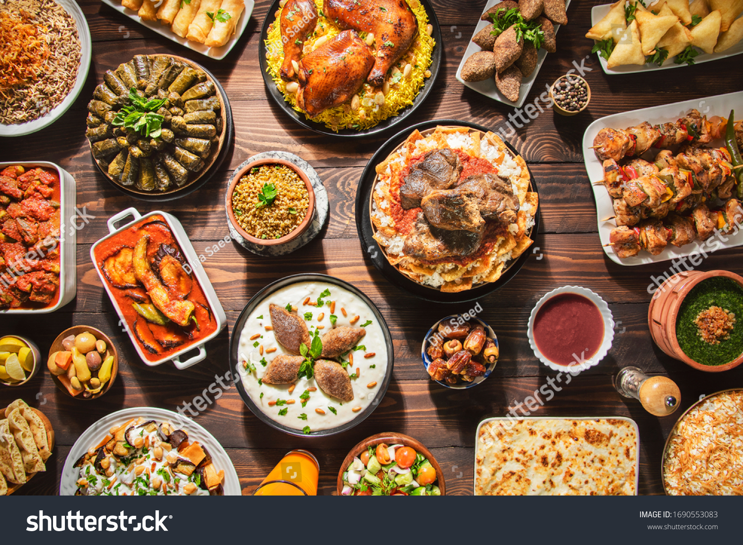 "Arabic Cuisine: Middle Eastern traditional lunch. It's also Ramadan ""Iftar"". The meal eaten by Muslims after sunset during Ramadan. Assorted of Arabic oriental dishes. top view with close up.  #1690553083"