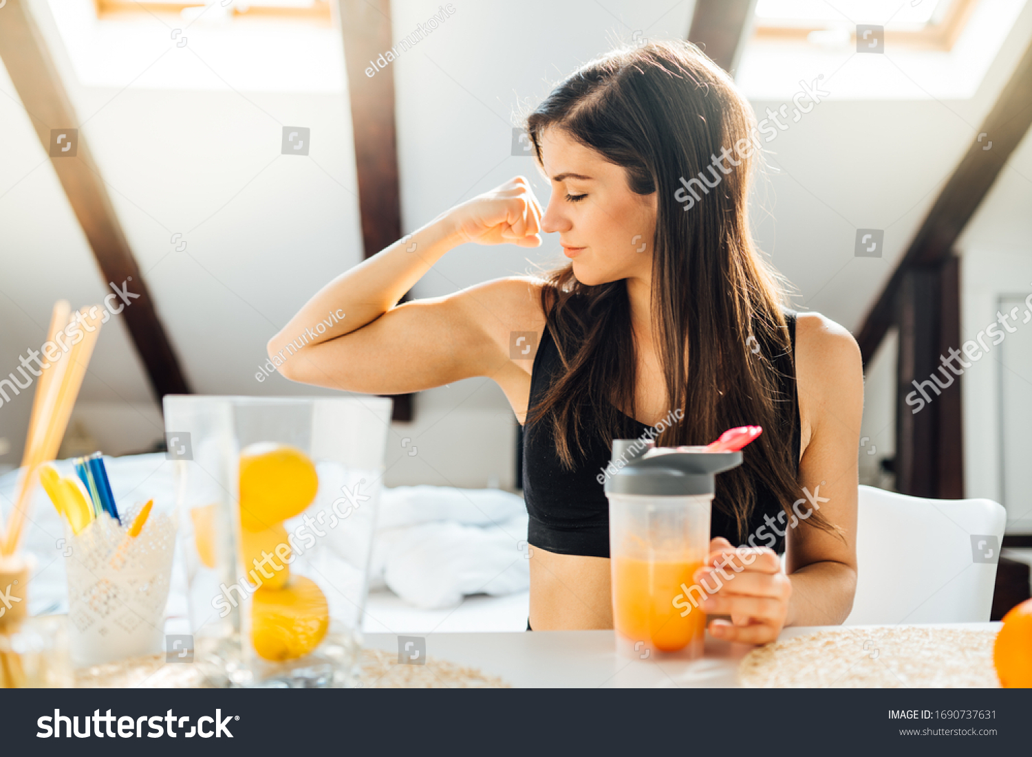 Woman at home drinking orange flavored amino acid vitamin powder.Keto supplement.After exercise liquid meal.Weight loss fitness nutrition diet.Immune system support.Organic citrus fruit drink #1690737631