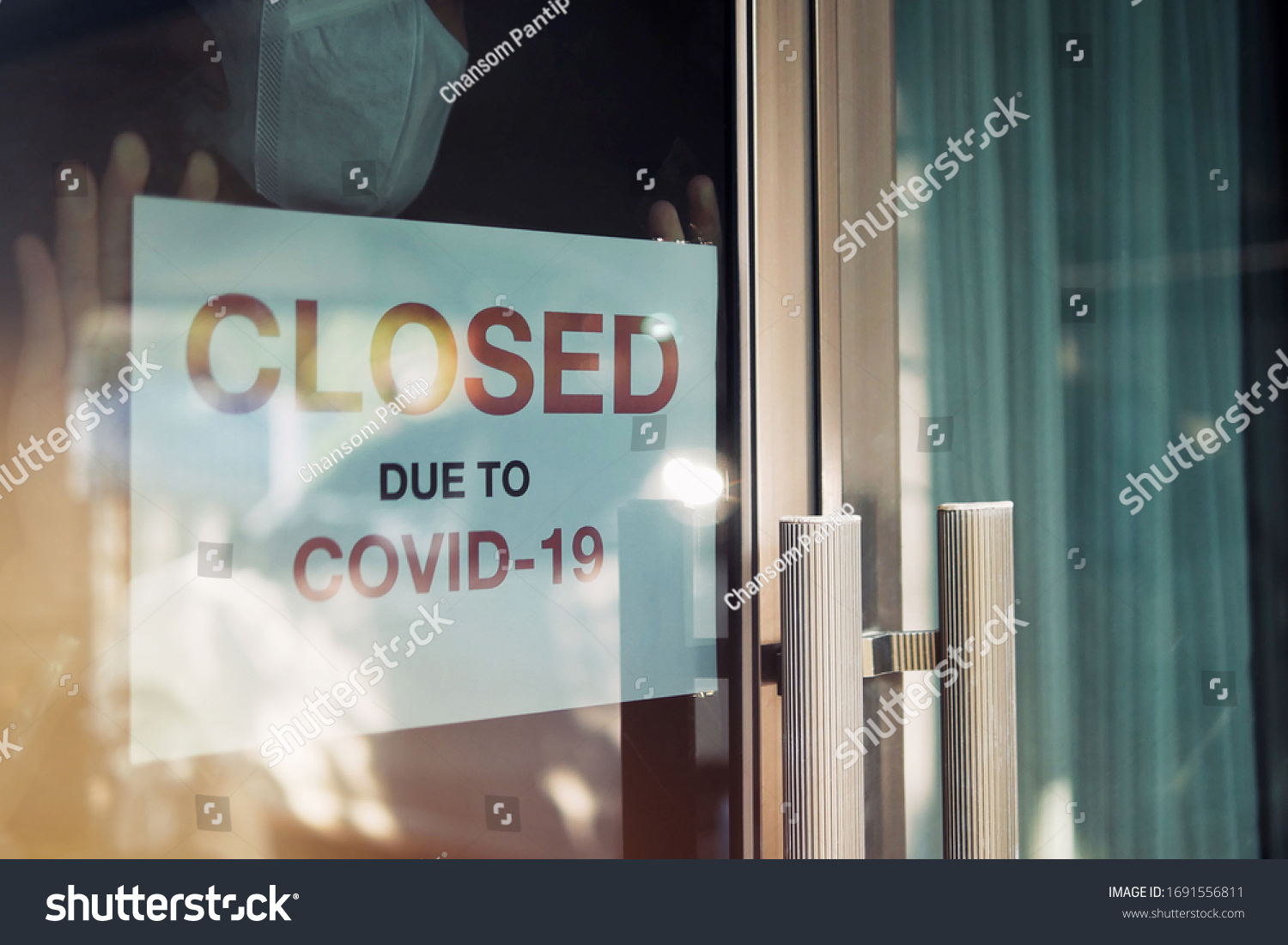 Business office or store shop is closed, bankrupt business due to the effect of novel Coronavirus (COVID-19) pandemic. Unidentified person wearing mask hanging closed sign in background on front door. #1691556811