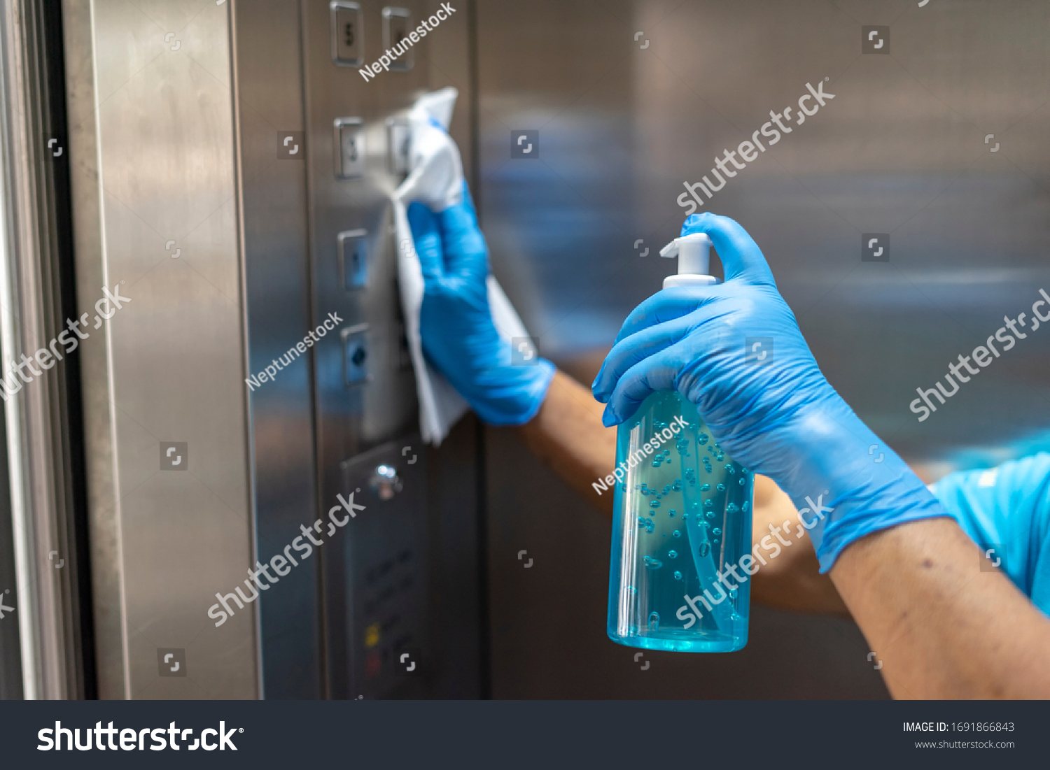 Closeup of old staff hand using wet wipe cleaning an elevator push button control panel with a blue sanitizer bottle.Disinfection,cleanliness and healthcare,Anti Corona virus,COVID-19.Selective focus. #1691866843