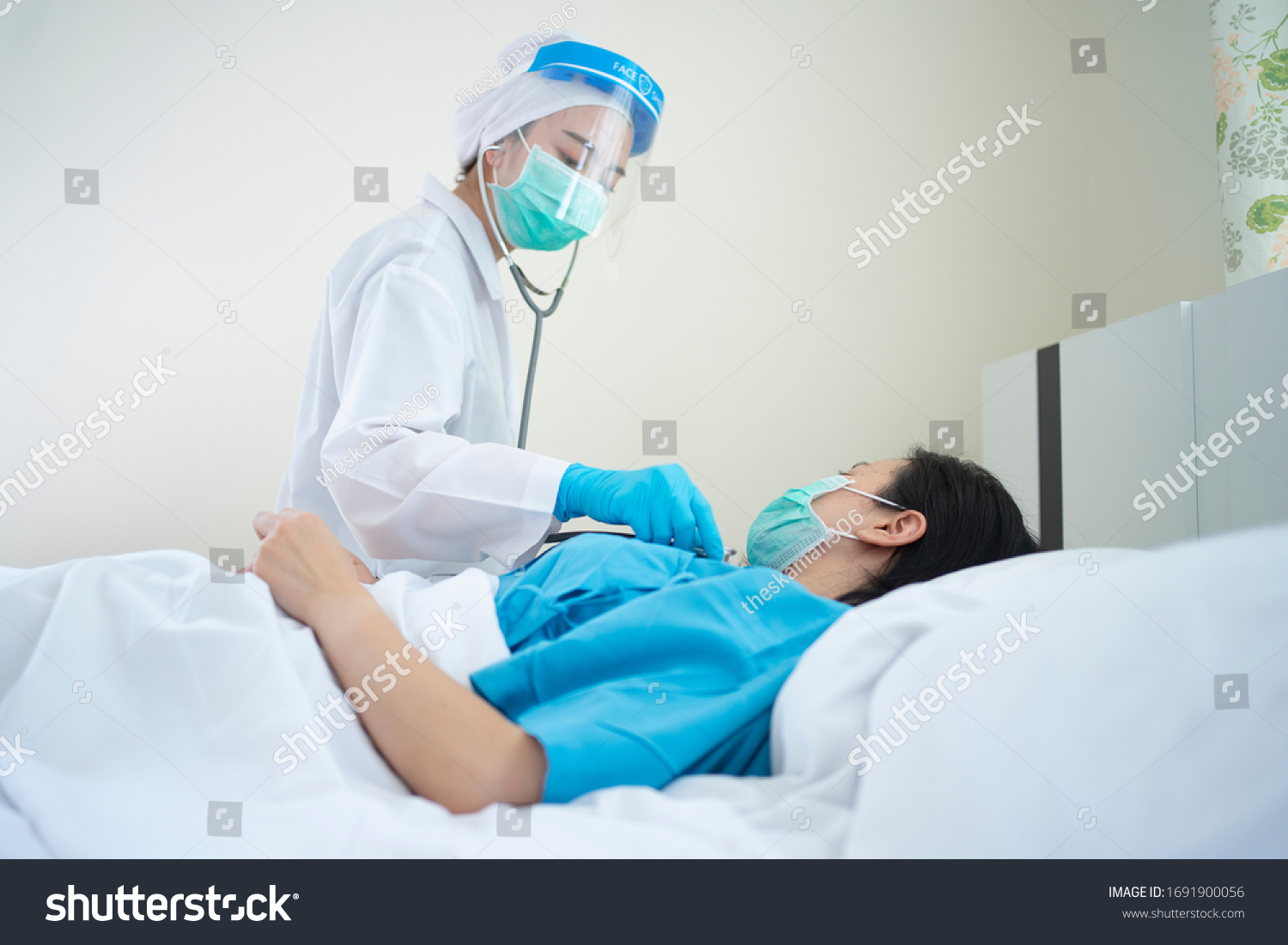 Doctor wearing PPE suit and Surgical mask and Checking infected patient in quarantine room Covid-19 (Coronavirus)Coronavirus outbreak or Covid-19, Concept of Covid-19 quarantine  #1691900056