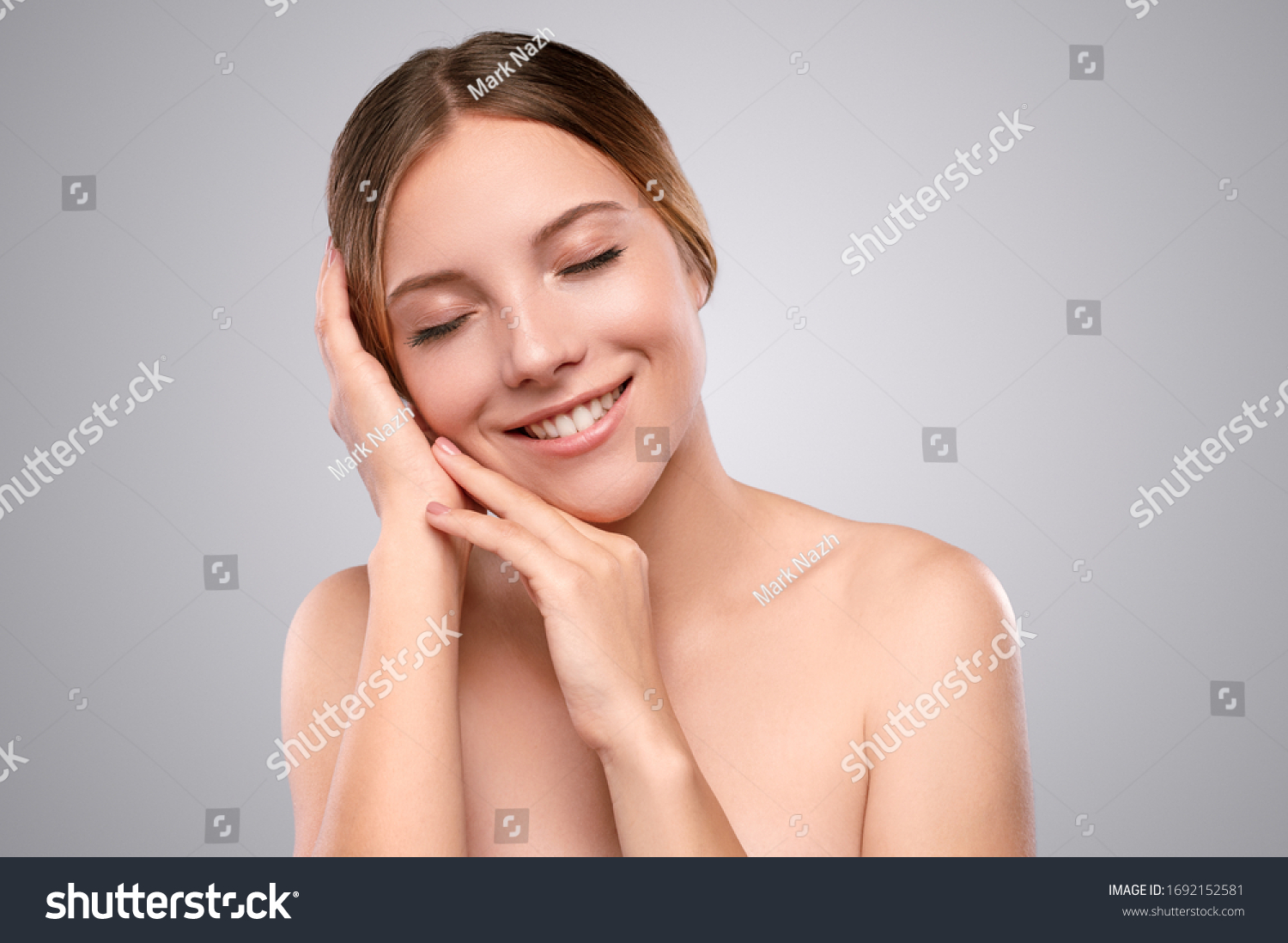 Young fair haired female model with bare shoulders and healthy soft skin touching face and smiling against gray background #1692152581