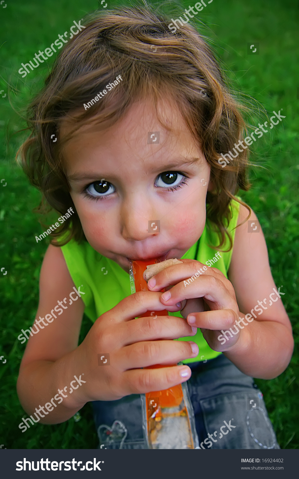 A Little Girls Eating Popsicle In The Grass
