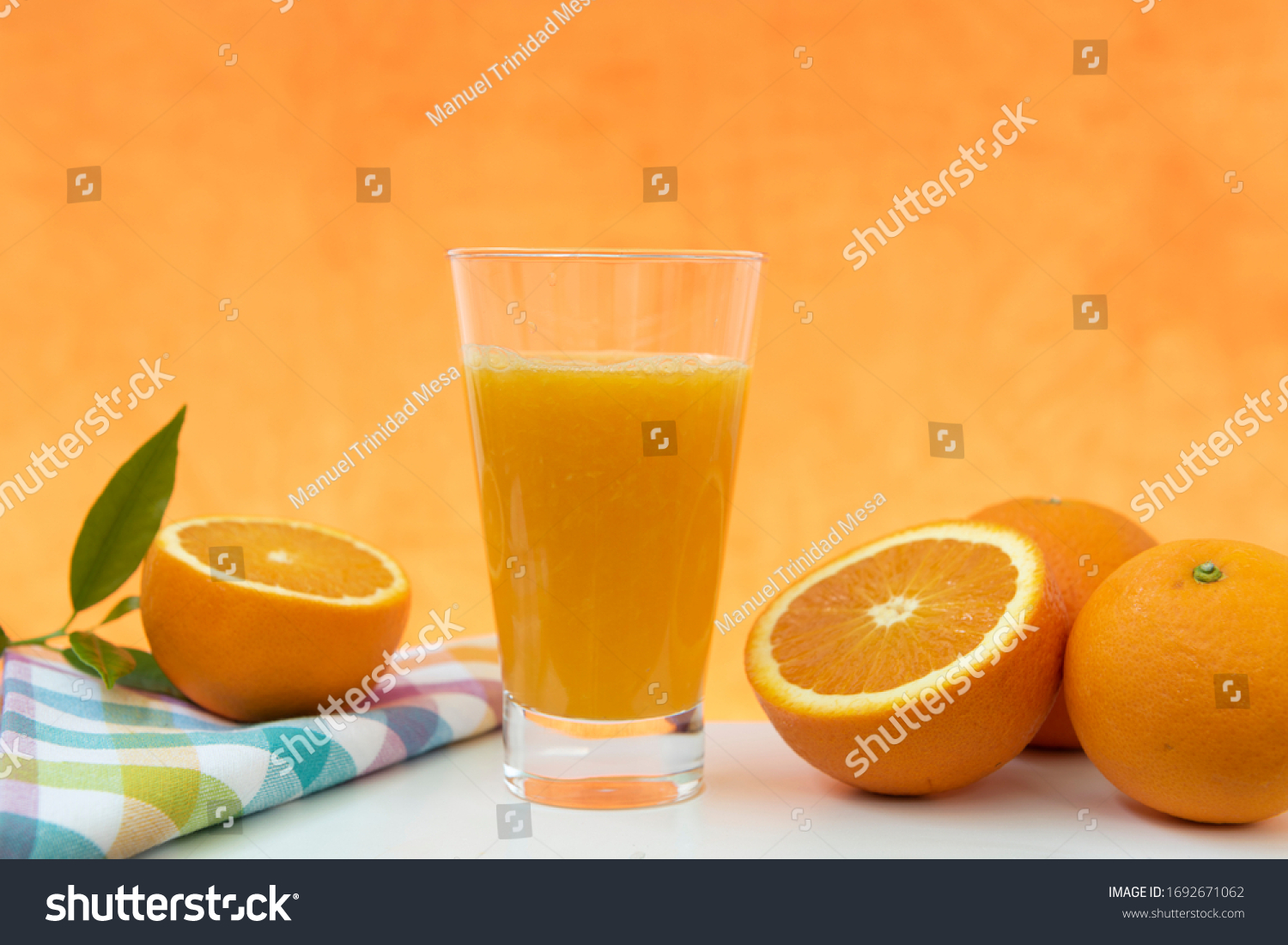 Glass of natural orange juice on orange background
