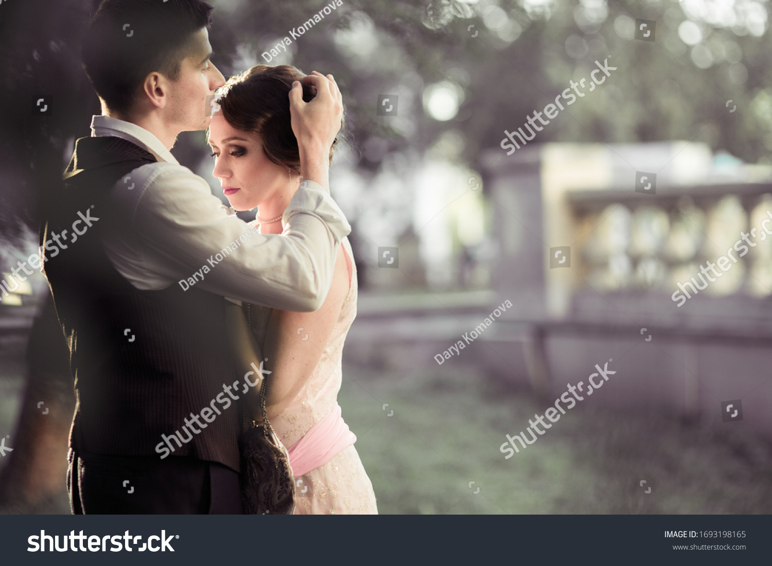 A young couple stands against a backdrop of large trees and a fence. A man adjusts the hair on a woman's head. Historical reconstruction #1693198165