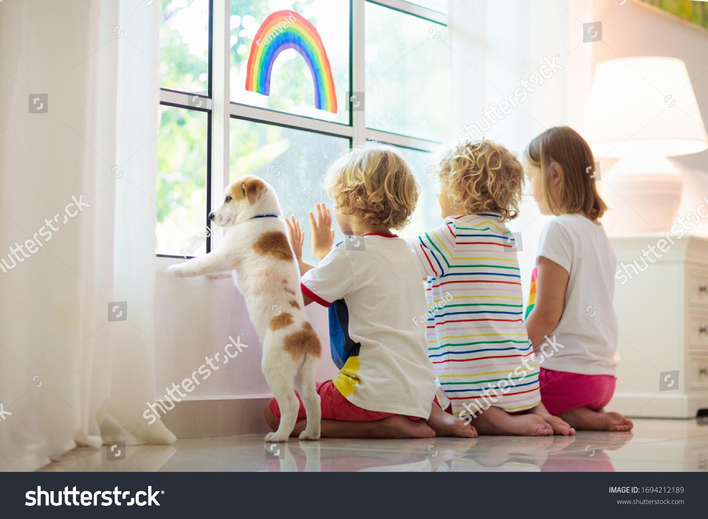Coronavirus quarantine. Stay home. Kids sitting at window. Children drawing rainbow sign of hope. Boy and girl during corona virus lockdown. Child and pet. Family isolation indoors. Disease prevention #1694212189