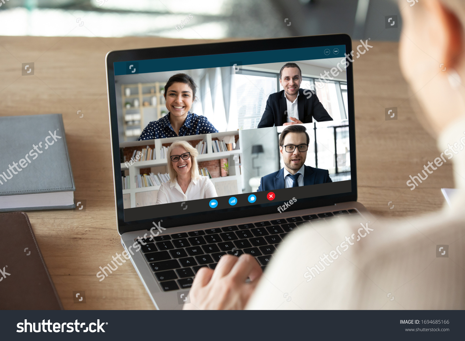 View over female shoulder at computer webcam screen view of four different age and ethnicity business people negotiating distantly using video conference app, video call virtual communication concept #1694685166