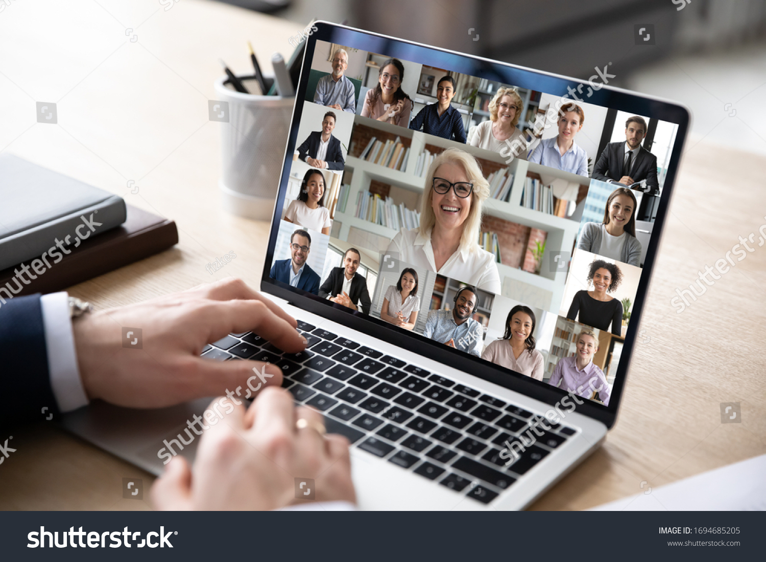 Businessman sit at desk use computer working on-line communicate distantly with colleagues by videoconferencing diverse people engaged in group video call, advertise worldwide virtual chat app concept #1694685205
