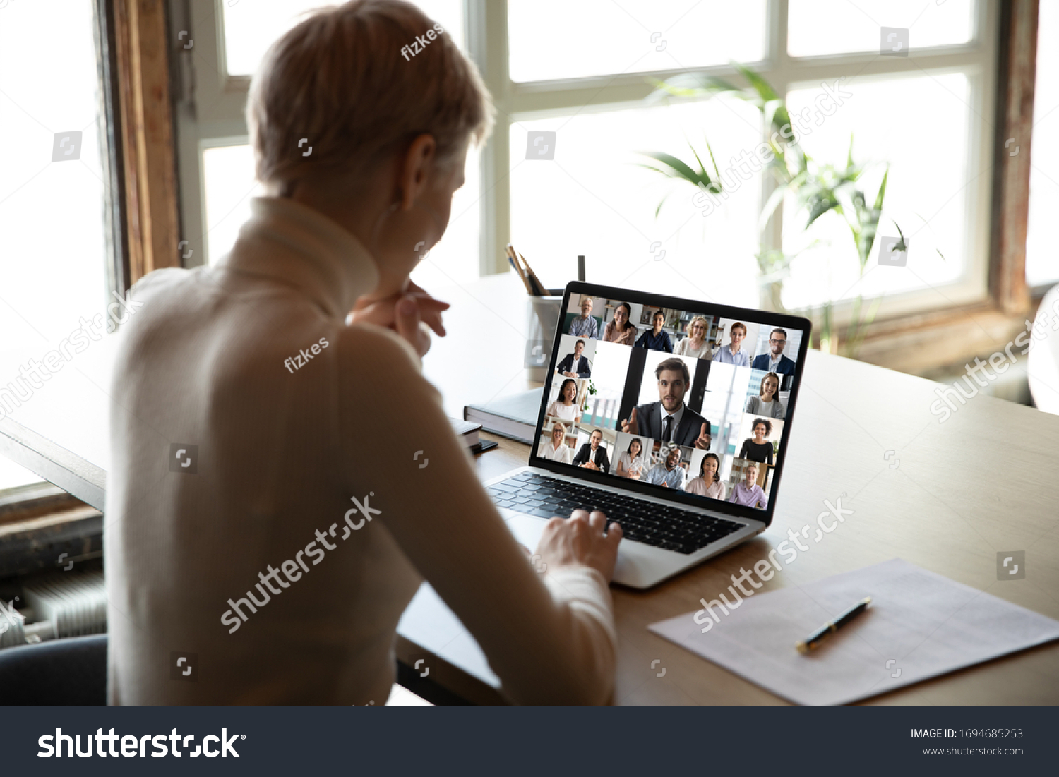 Rear view woman sit at desk learns new videoconference app online review, look at pc screen take part in group video call with corporate staff brainstorm distantly, study, work use modern tech concept #1694685253