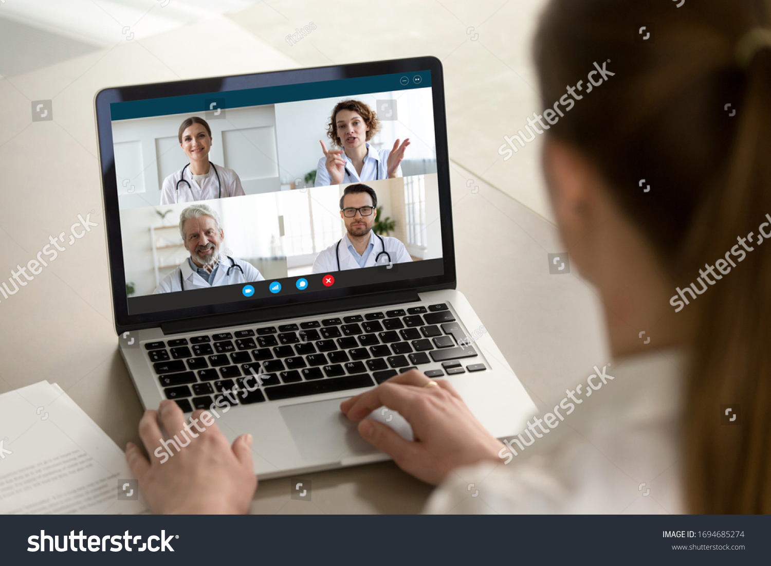 View over client shoulder sit at desk receive medical consultation on-line from diverse specialists. Woman listen doctors about corona virus precautionary measures, videoconference laptop webcam view #1694685274