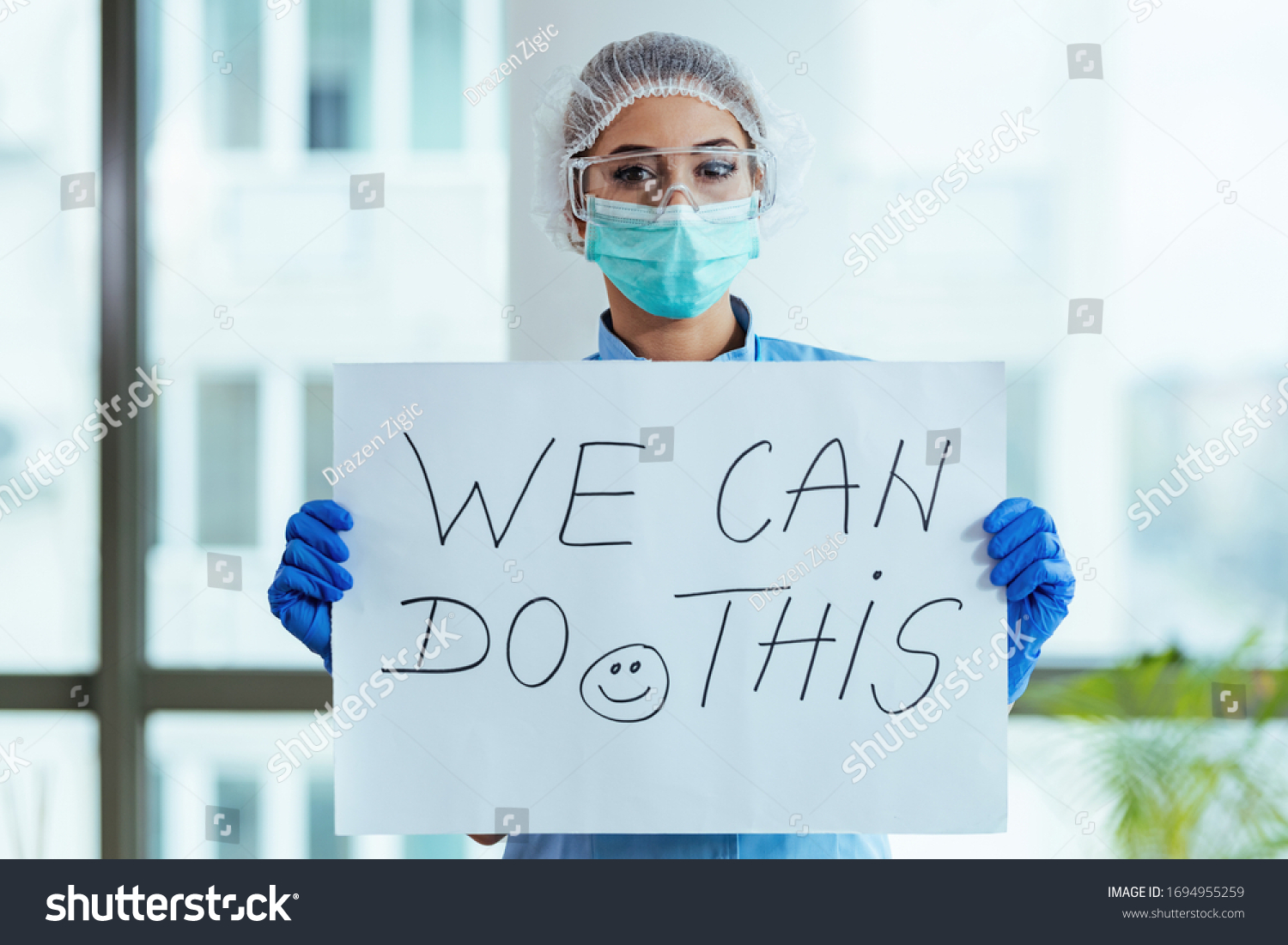 Healthcare worker holding placard with supportive 'we can do this' message while standing in the hospital.  #1694955259