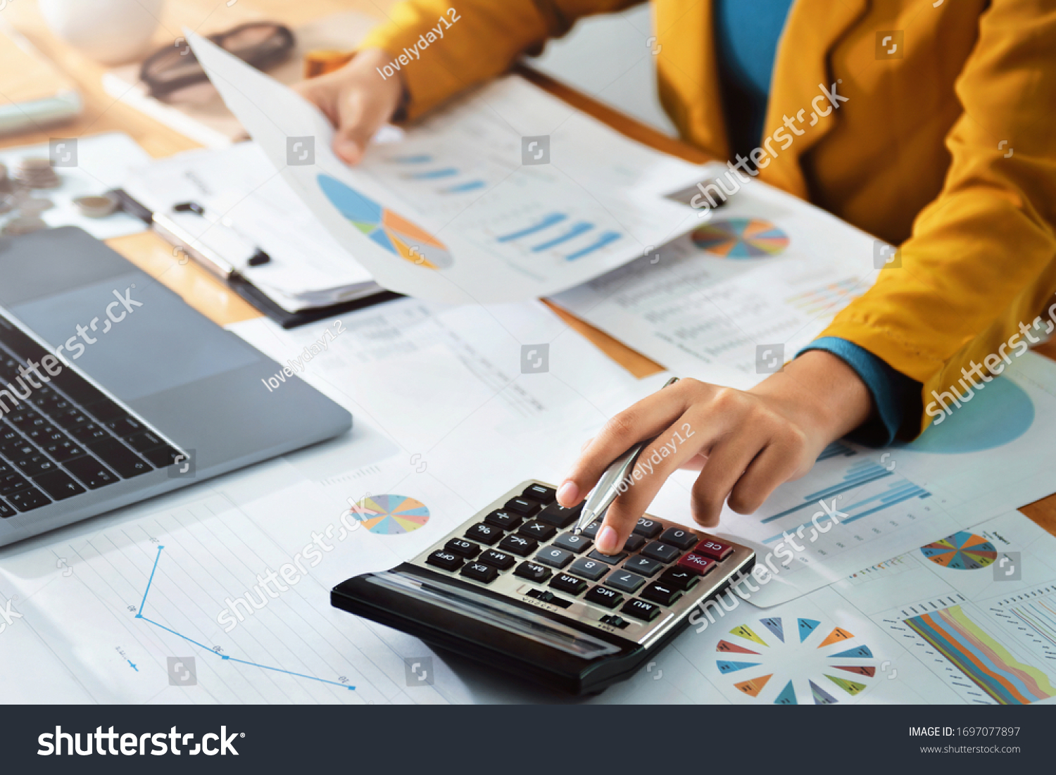 Woman accountant use calculator and computer with holding pen on #1697077897