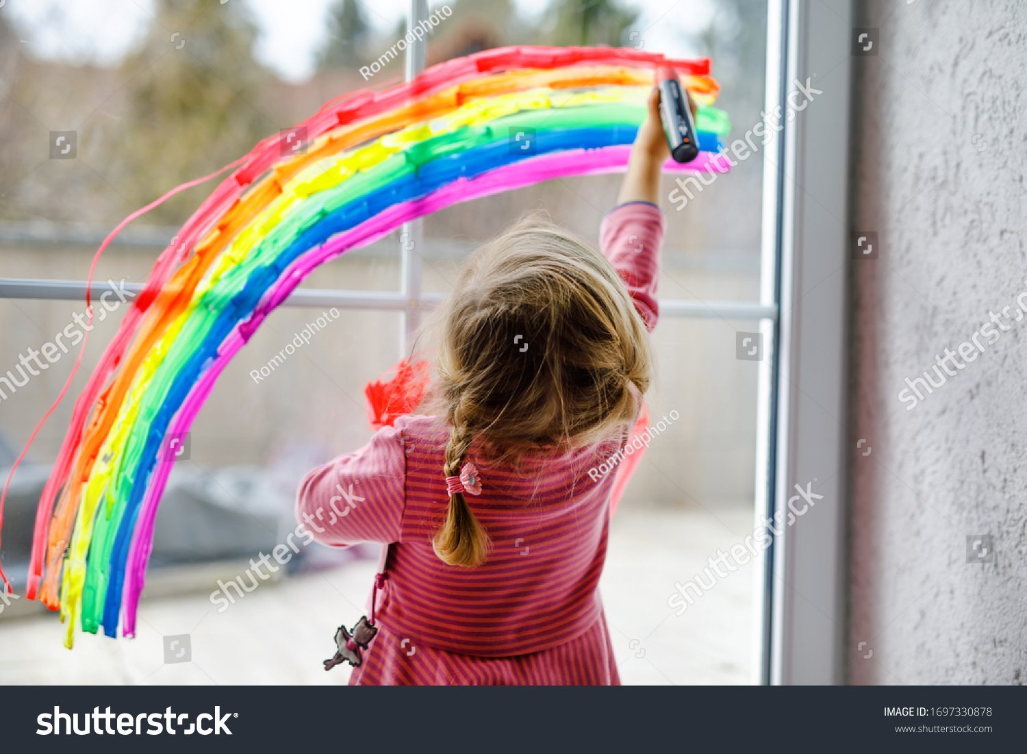 Adoralbe little toddler girl with rainbow painted with colorful window color during pandemic coronavirus quarantine. Child painting rainbows around the world with the words Let's all be well. #1697330878