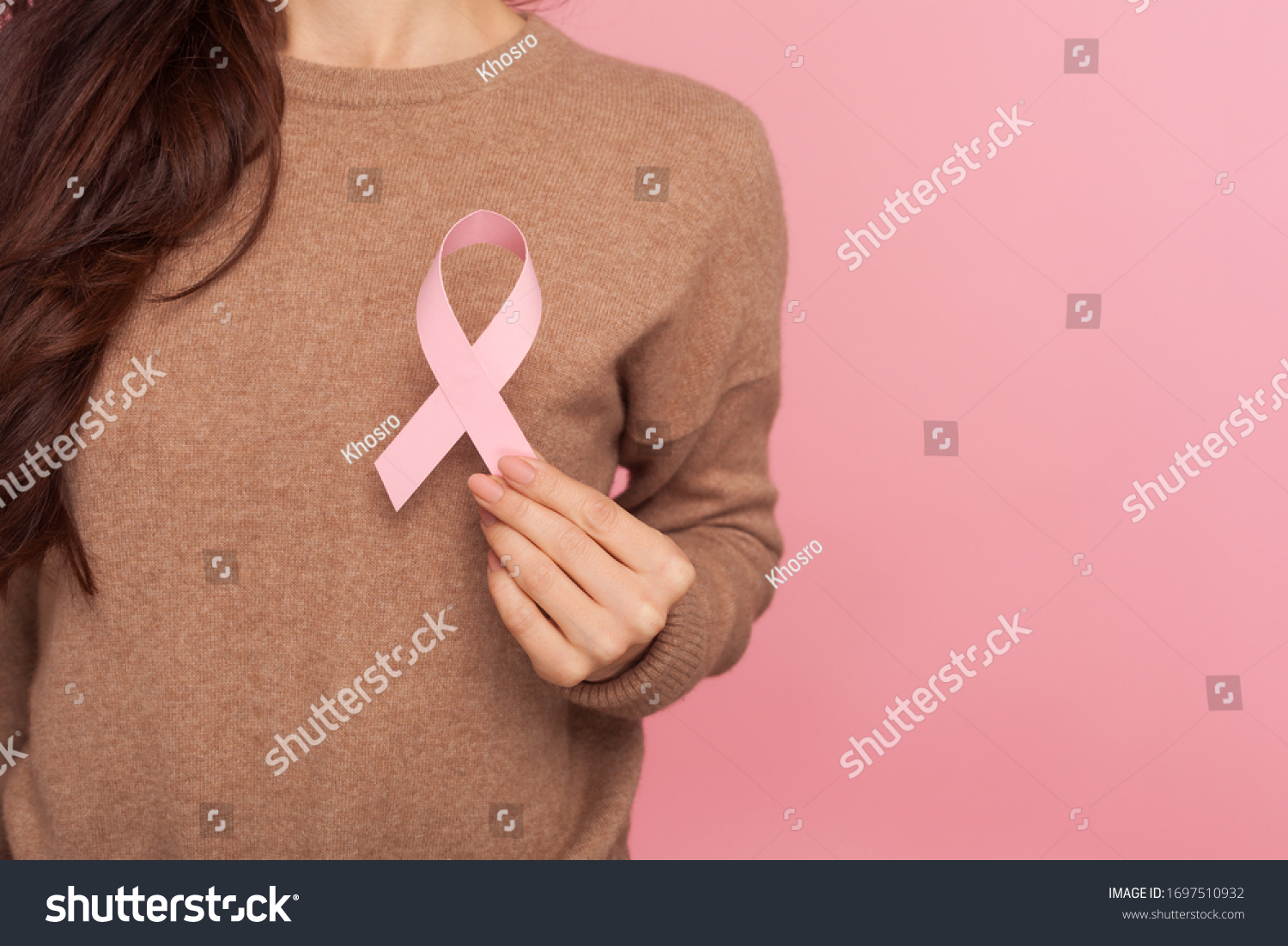 Female health check awareness. Closeup of young woman in pullover holding pink ribbon, symbol of breast cancer, timely diagnosis, support of oncology patients. studio shot isolated on pink background #1697510932