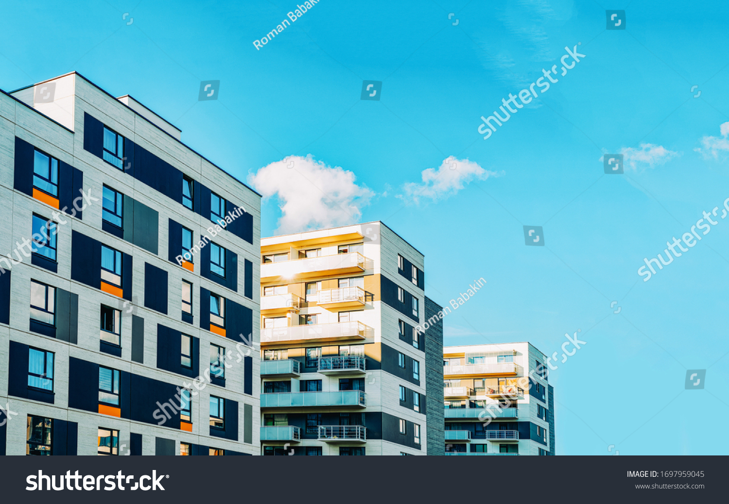Detail in Modern residential flat apartment building exterior. Fragment of New luxury house and home complex. Part of City Real estate property and condo architecture. Copy space. Blue sky #1697959045