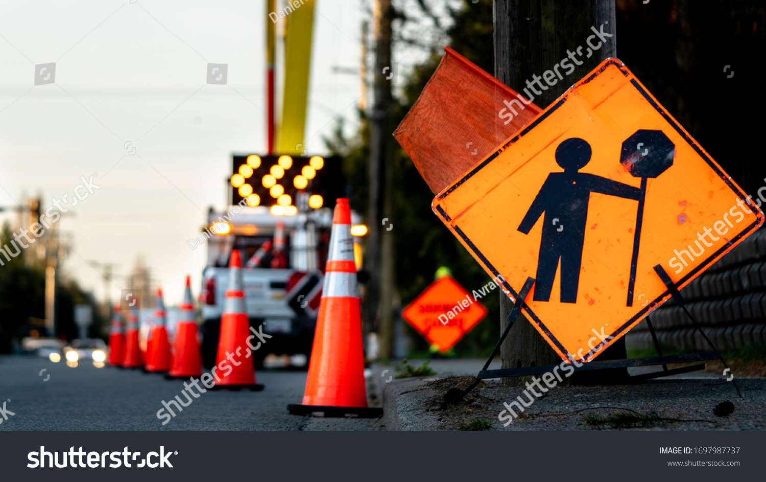 Lane closure on a busy road due to maintenance, signs detour traffic temporary street work orange lighted arrow, barrels and cones. #1697987737