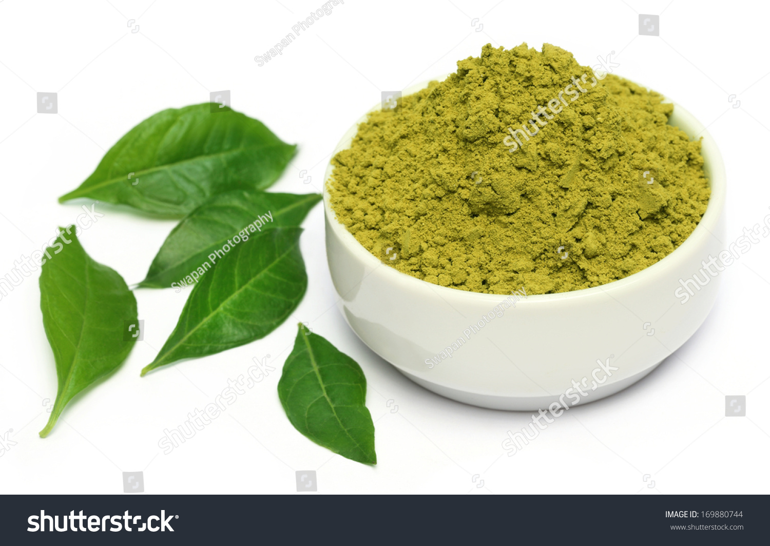 Henna leaves with powder on ceramic bowl over white background #3F761A