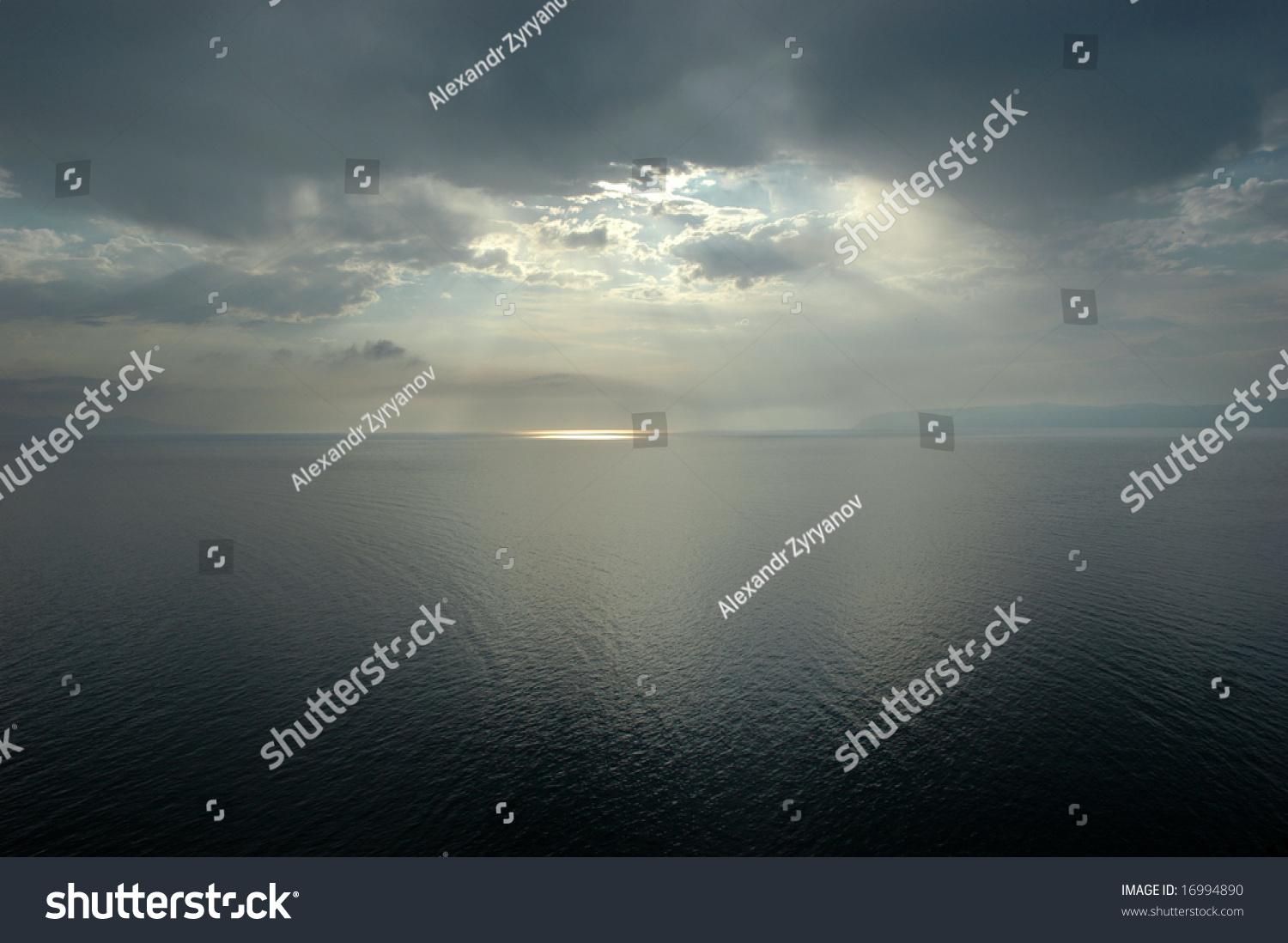 stock-photo-sea-and-sun-lighting-through