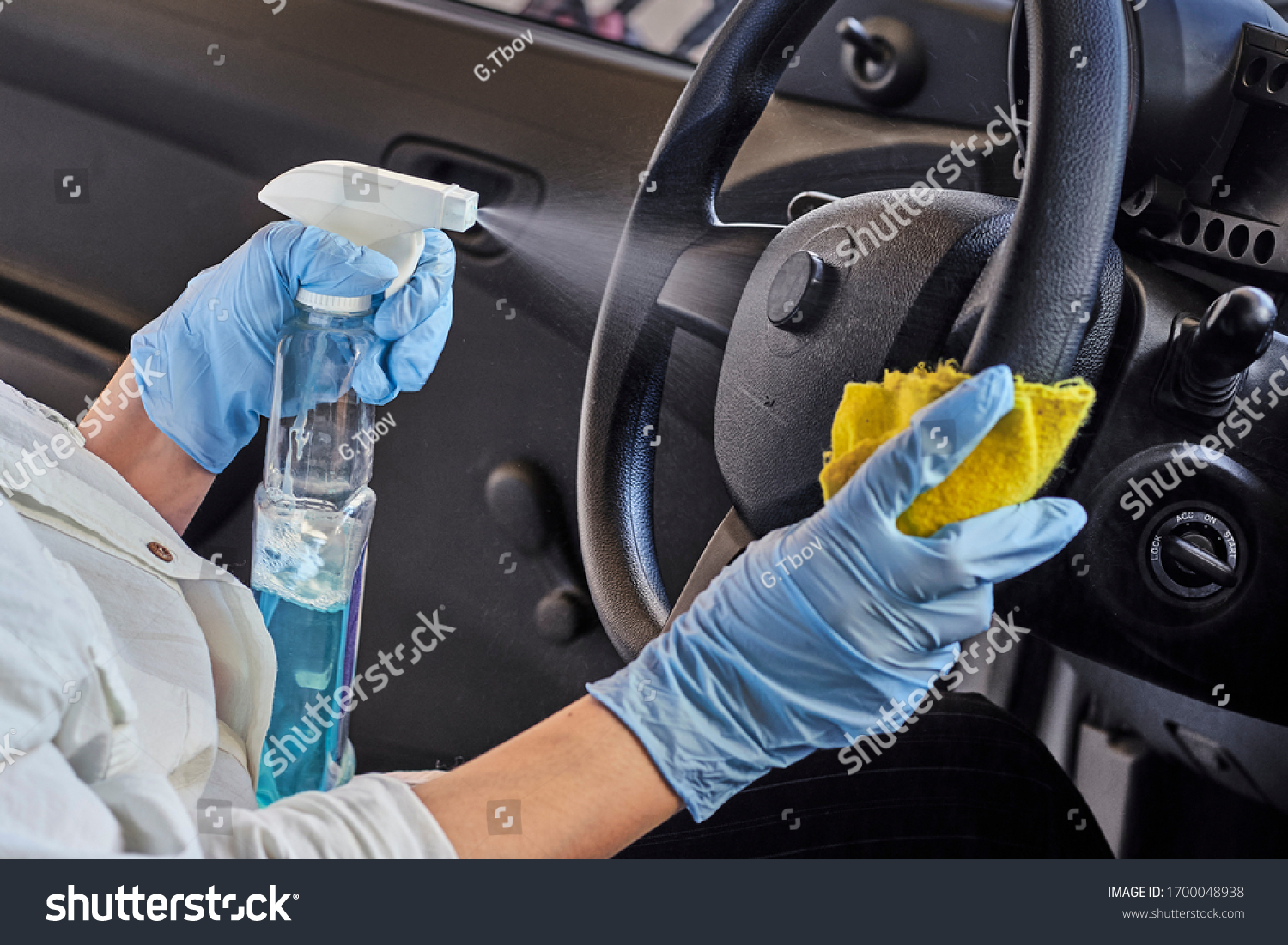 Woman in rubber protective glove disinfecting car steering wheel. Cleaning vehicle inside for protection from Coronavirus disease. Epidemic Outbreak
