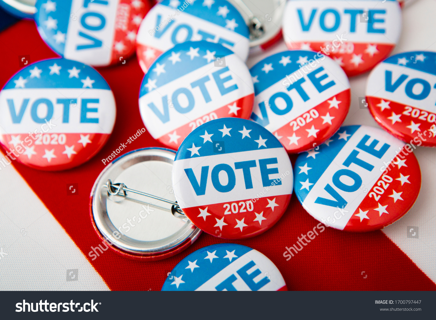 Election 2020 in the USA. Variety Of Presidential Election Buttons on American flag #1700797447