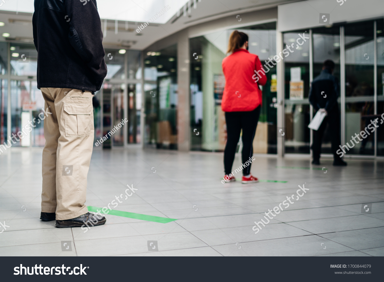 People standing in line front of bank/store due to coronavirus pandemic safety guideline.COVID-19 safe social distancing practice.Quarantine financial crisis,banking,loans.Spaced out queue.Crowd-limit #1700844079