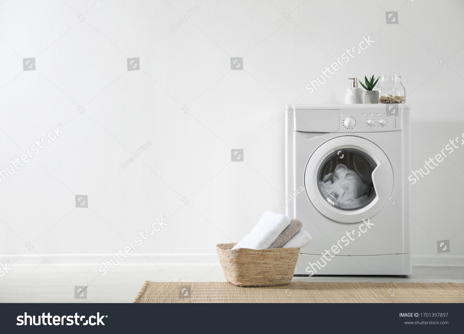 Modern washing machine and laundry basket near white wall indoors, space for text. Bathroom interior #1701397897