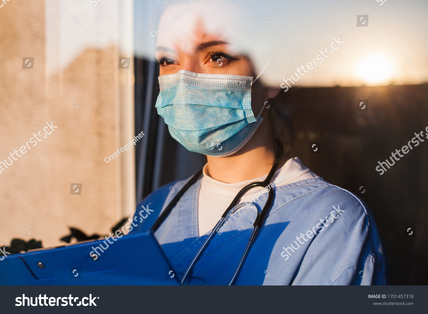 Young sad female caucasian UK US NHS EMS doctor carer looking through ICU window,fear uncertainty in eyes,wearing face mask gazing at sun,hope faith in overcoming Coronavirus COVID-19 pandemic crisis  #1701457318