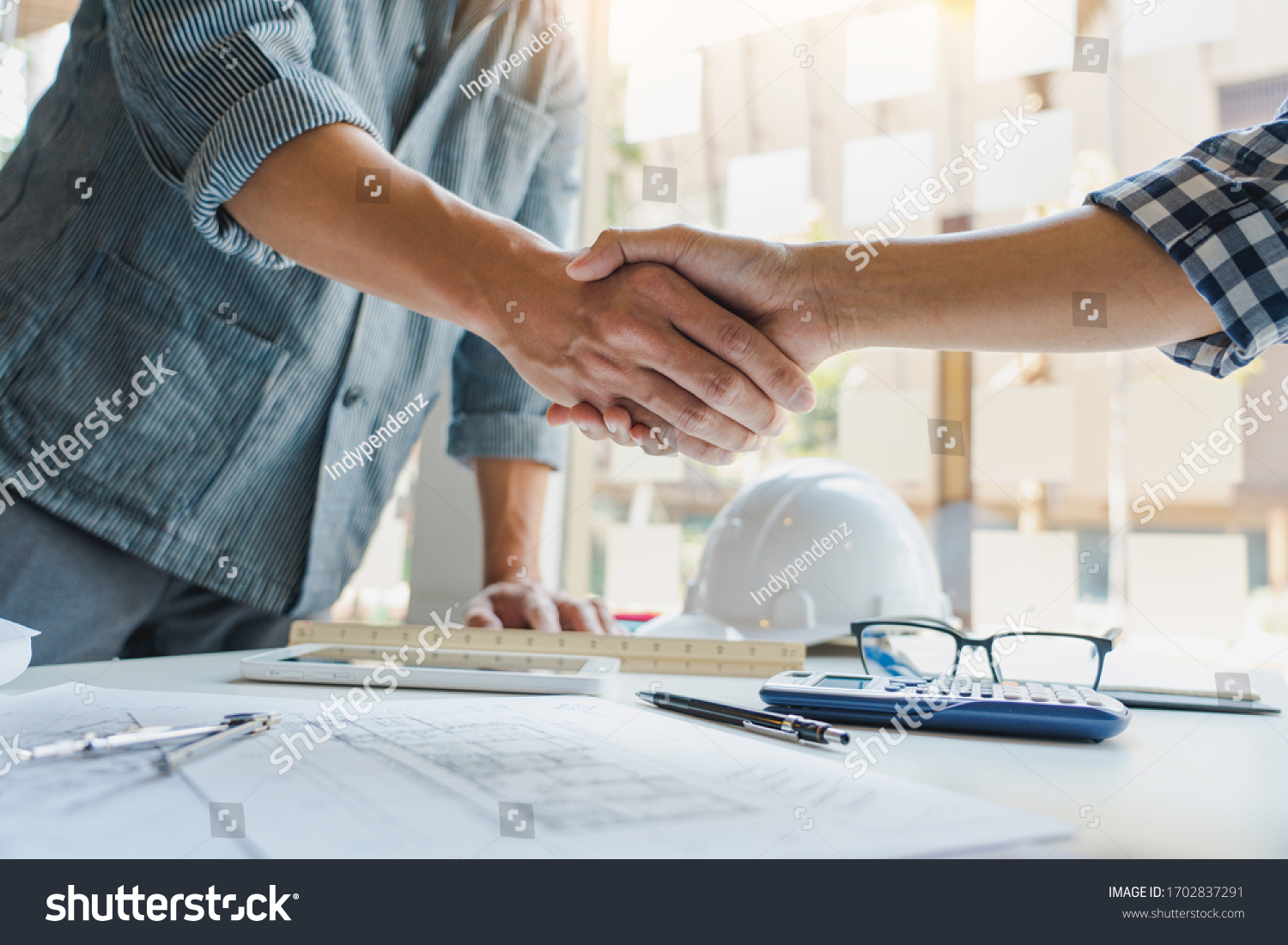 Architect and engineer construction workers shaking hands while working for teamwork and cooperation concept after finish an agreement in the office construction site, success collaboration concept #1702837291