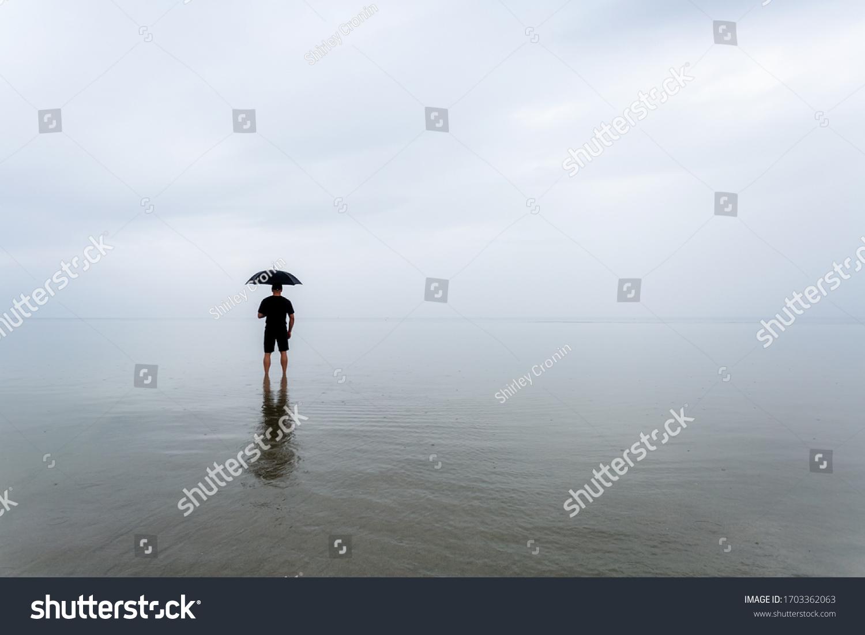stock-photo-man-with-umbrella-at-the-bea