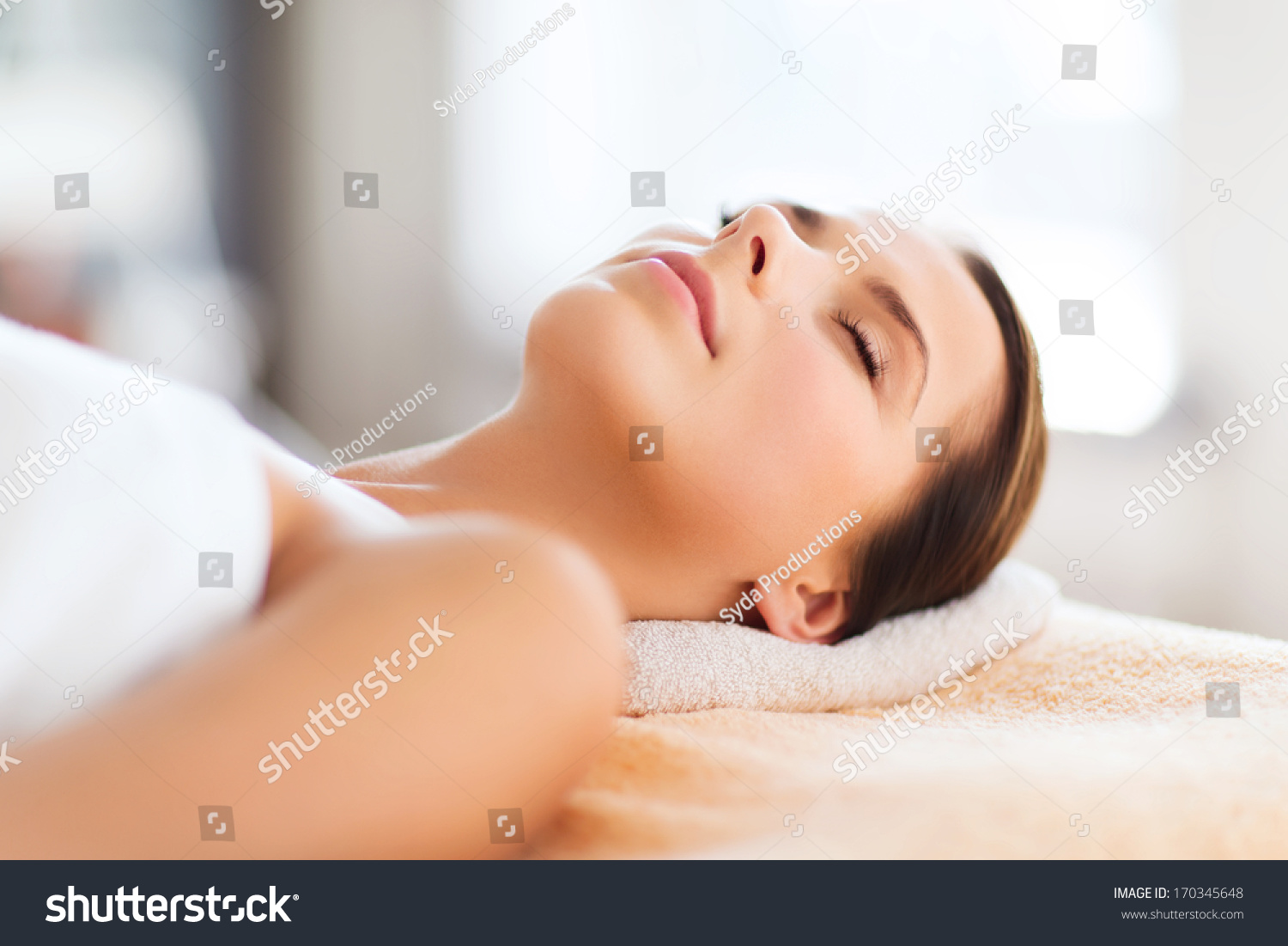 beauty and spa concept beautiful woman in spa salon lying on the massage desk stock photo. Black Bedroom Furniture Sets. Home Design Ideas
