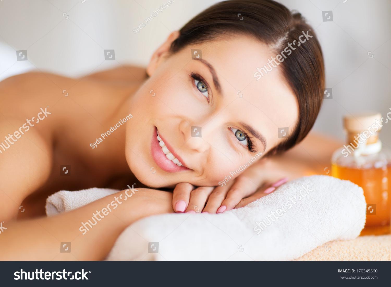beauty and spa concept happy woman in spa salon lying on the massage desk photo libre de. Black Bedroom Furniture Sets. Home Design Ideas