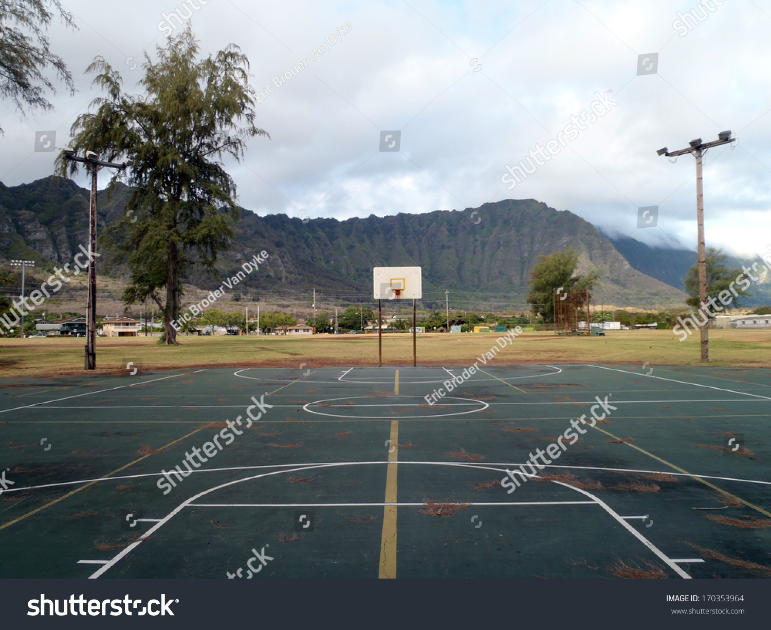 old rusty empty outdoor basketball court with lights on wooden poles and pine needles on the