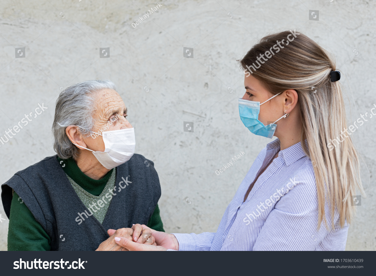 Portrait of friendly caregiver posing with elderly ill woman wearing surgical mask because of covid-19 pandemic #1703610439