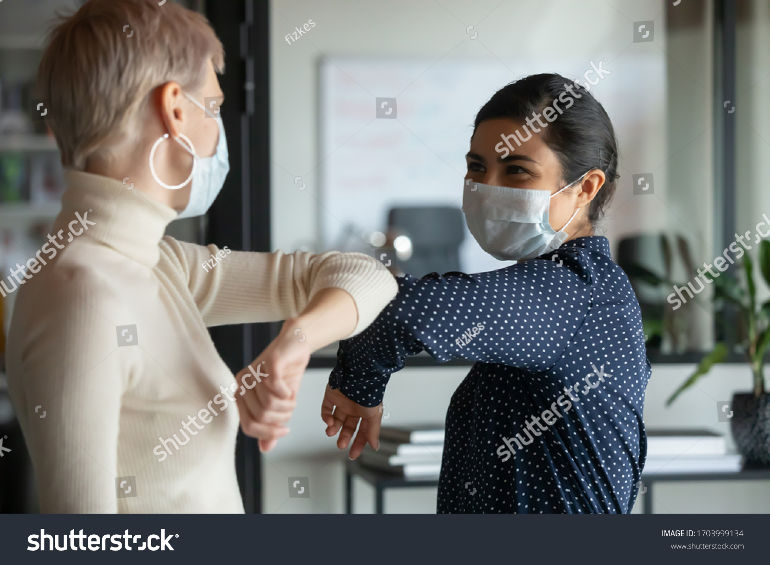 Smiling diverse female colleagues wearing protective face masks greeting bumping elbows at workplace, woman coworkers in facial covers protect from COVID-19 coronavirus in office, healthcare concept #1703999134
