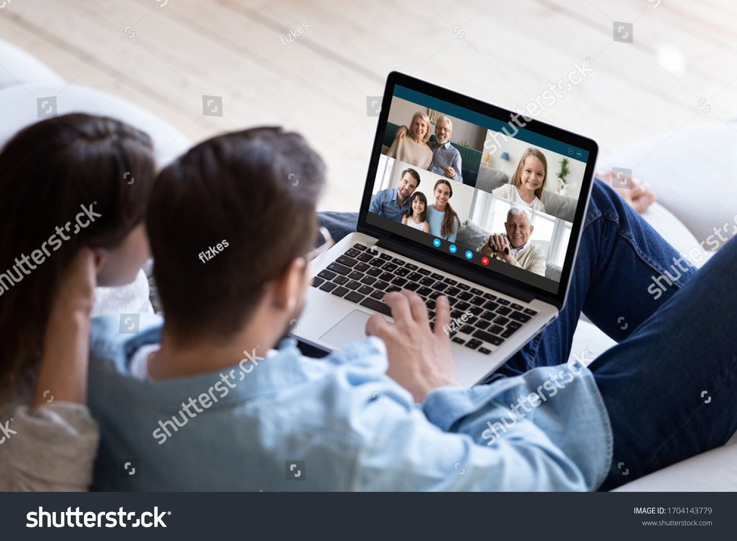 Rear back view married couple resting and chatting with relatives via videoconference videocall application, laptop screen view over spouse shoulder. Distant virtual communication, modern tech concept #1704143779