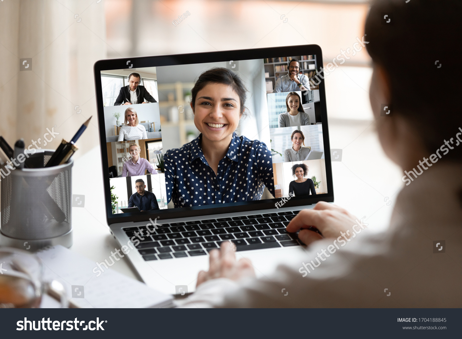 Woman sit at desk looking at computer screen where collage of diverse people webcam view. Indian ethnicity young woman lead video call distant chat, group of different mates using videoconference app #1704188845