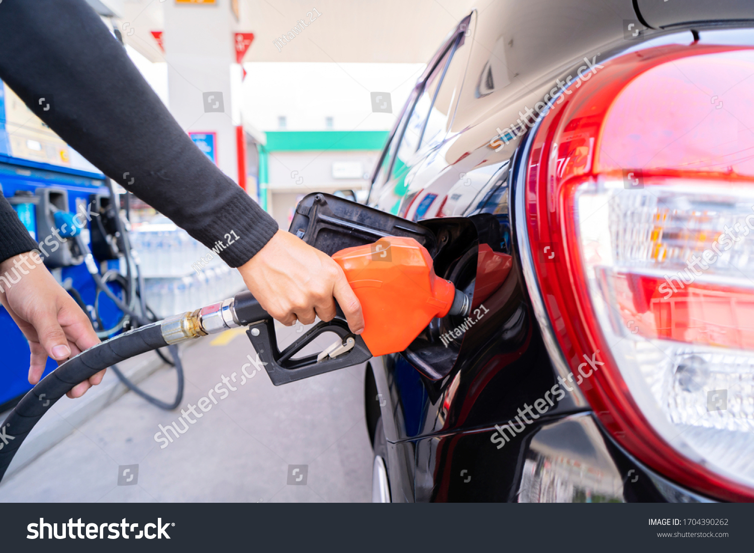 Refuel cars at the fuel pump. The driver hands, refuel and pump the car's gasoline with fuel at the petrol station. Car refueling at a gas station Gas station #1704390262