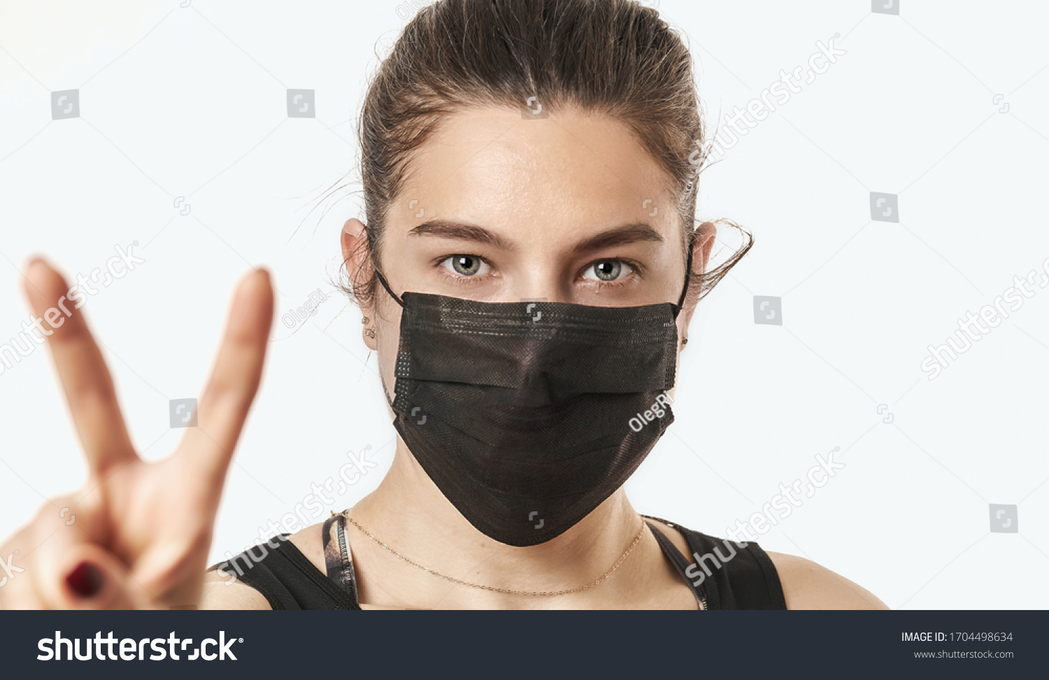 A close-up portrait of a pretty female wearing a surgical mask isolated on a white background #1704498634