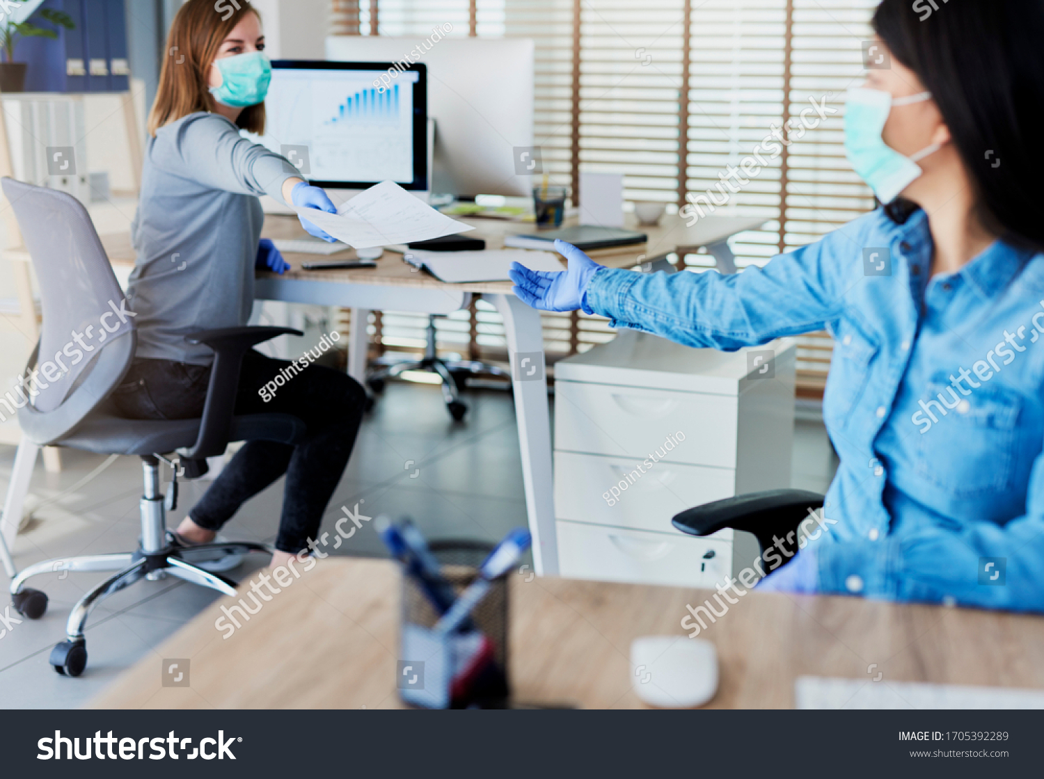 Two people in office passing documents with keeping a distance