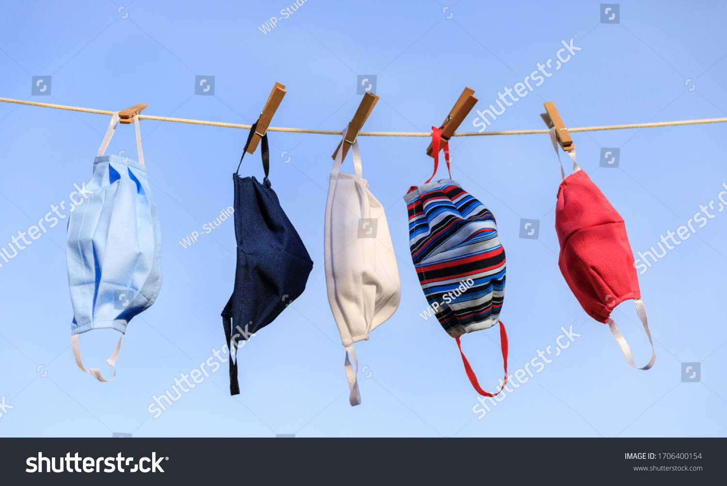Drying mask hanging under the sun after use for disinfecting. Hygienic mask hanging on the rack outdoor after being washed for cleanness and hygiene during Covid-19 virus outbreak #1706400154