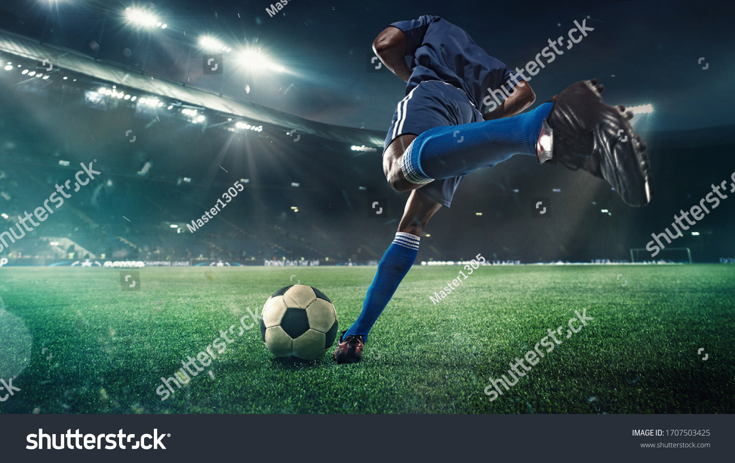 Professional football or soccer player in action on stadium with flashlights, kicking ball for winning goal, wide angle. Concept of sport, competition, motion, overcoming. Field presence effect. #1707503425