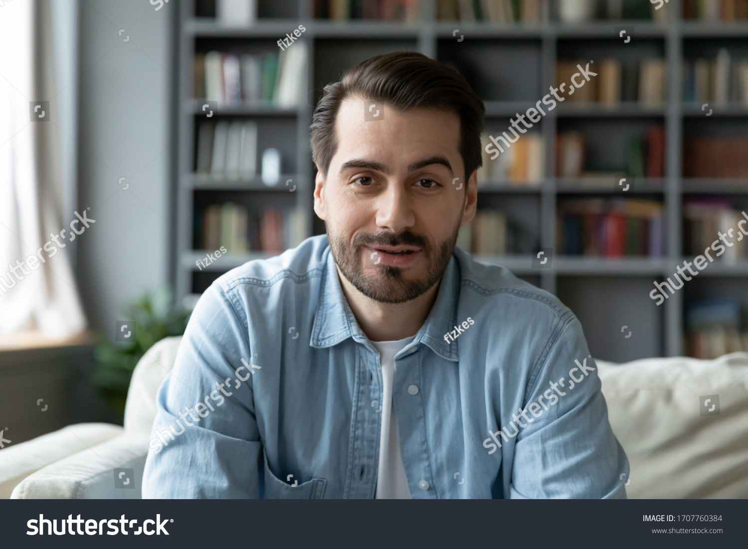Head shot millennial guy sit on sofa in living room makes video call looks at camera, conversation by distant videocall, distance hiring job interview process, tutor and trainee study on-line concept #1707760384