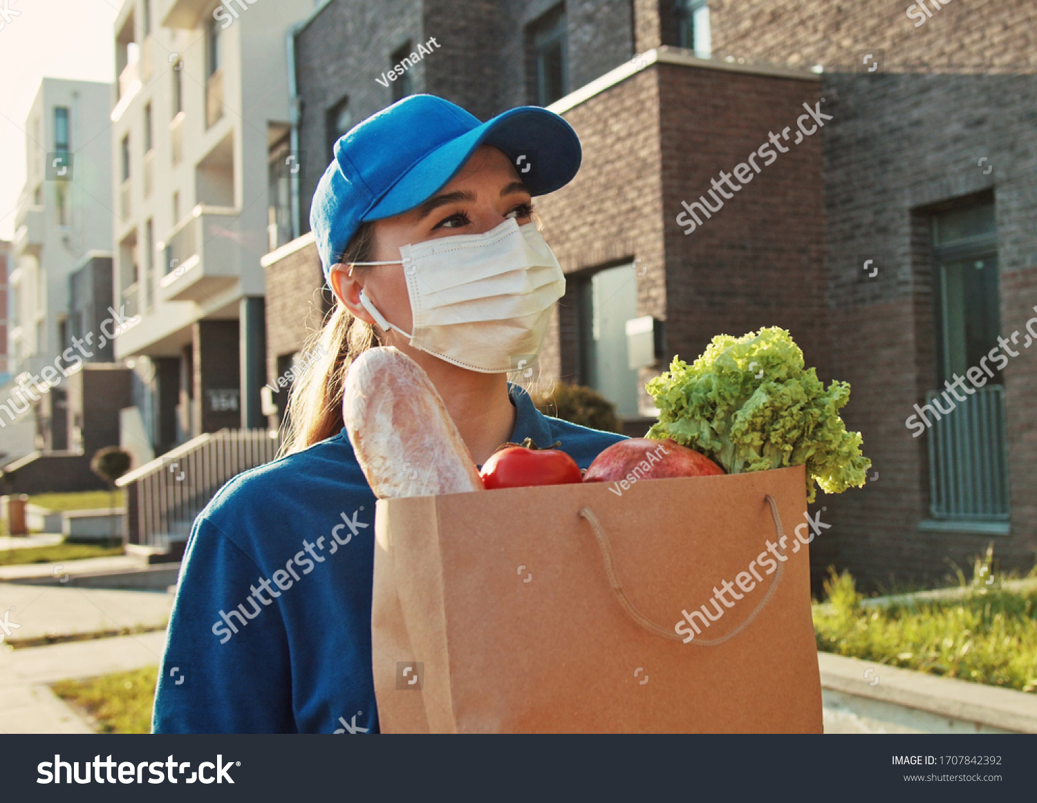 Caucasian young pretty woman, delivery worker in bluetooth headphones, cap and medical mask walking the street and carrying packet with fresh food. Female beautiful courier going to deliver grocery. #1707842392