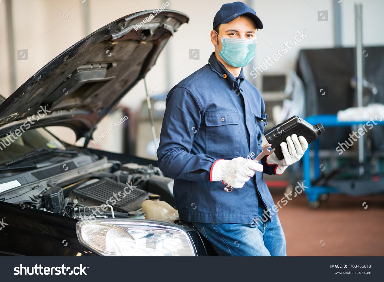 Masked car mechanic holding a jug of motor oil during coronavirus pandemic #1708466818