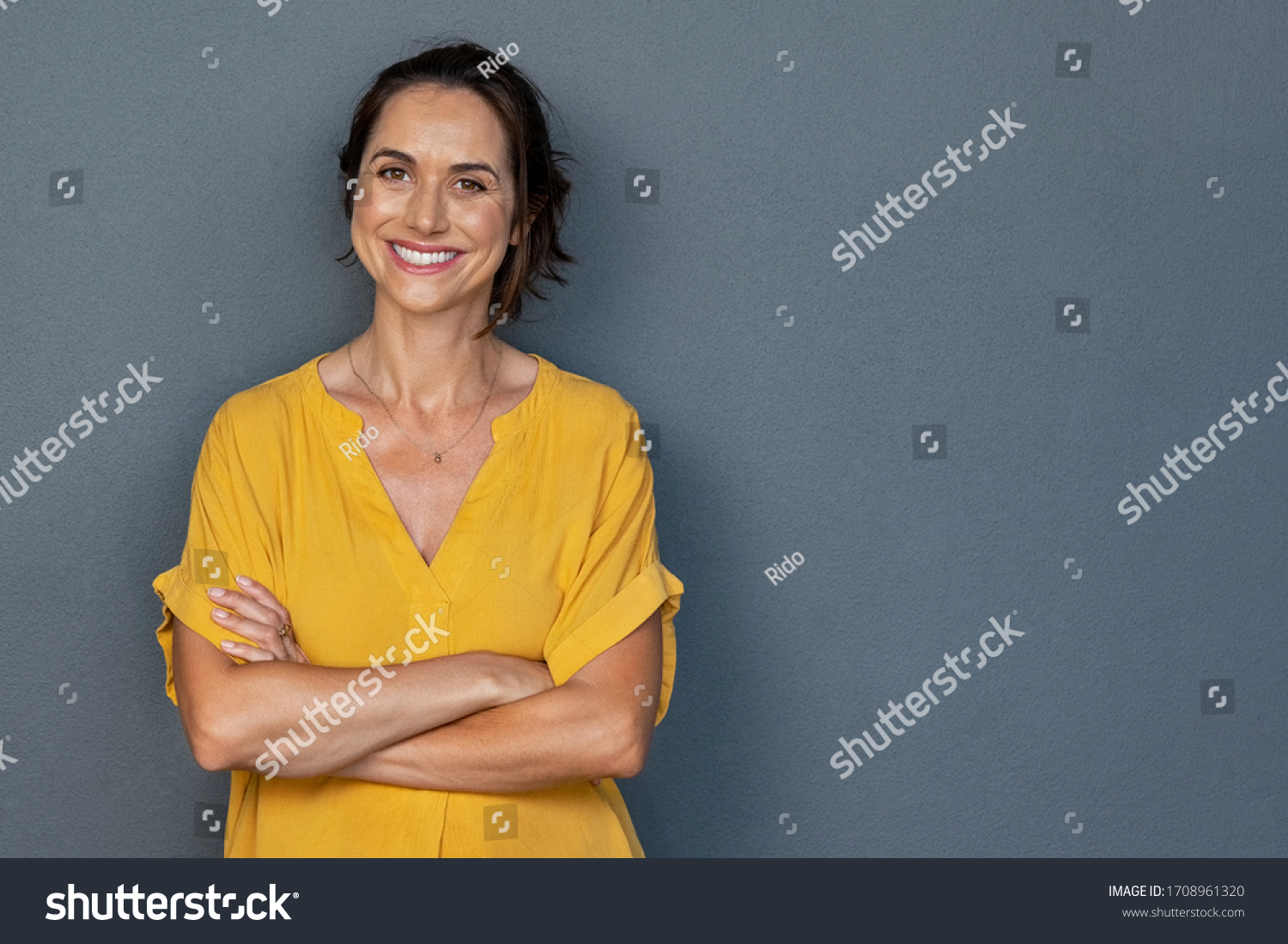 Confident mature woman with crossed arms in casual clothing with copy space. Successful smiling woman with big grin looking at camera. Beautiful positive businesswoman standing against grey background #1708961320