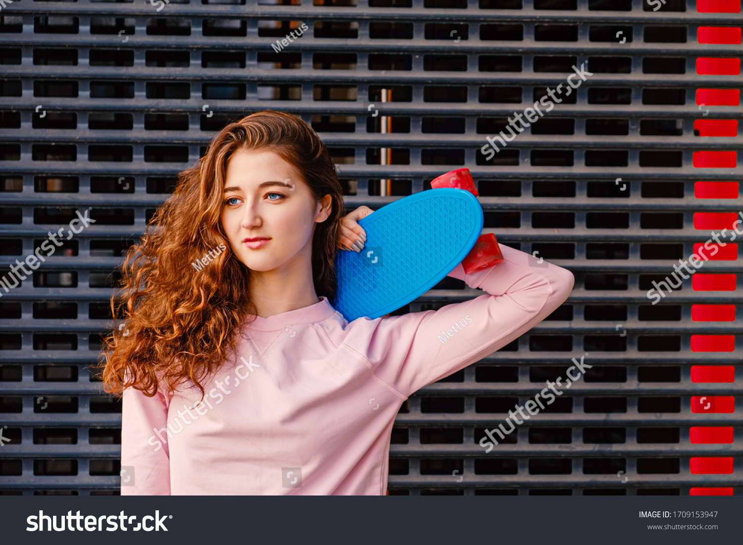 A girl with long curly brown hair holds a blue skateboard on her shoulder. She stands with blank expression on her face in front of an iron grating in a skateboard park.