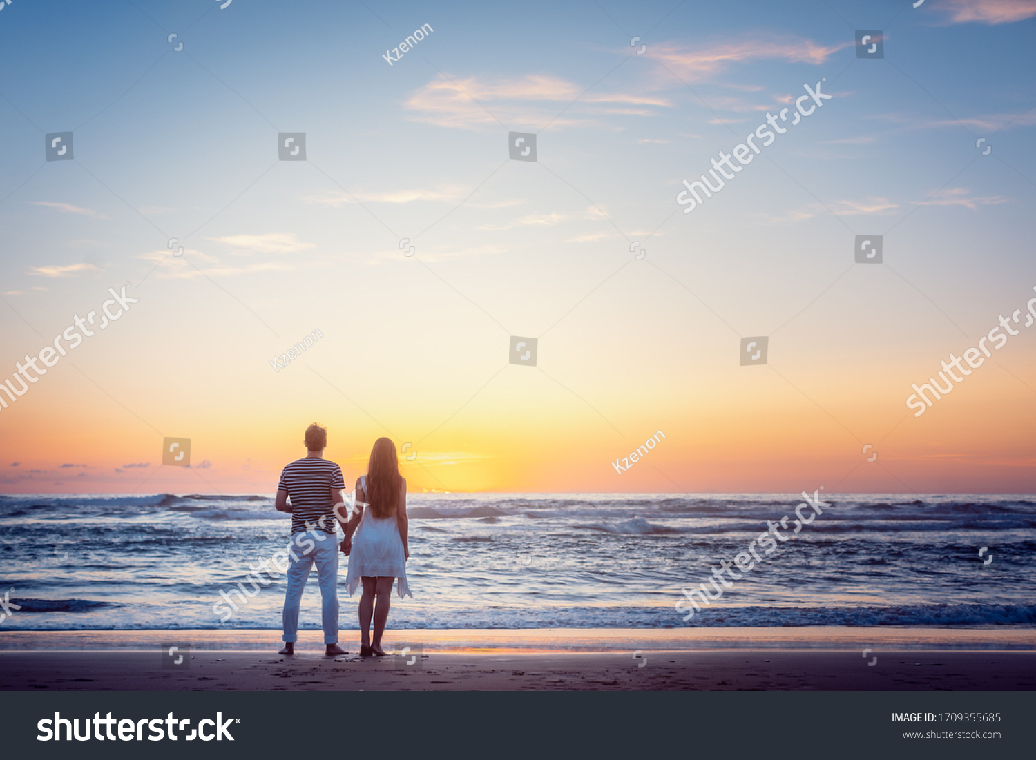 Romantic couple holding hands in their vacation standing on a beach by the sea #1709355685